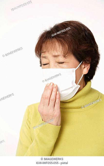 Senior woman wearing surgical mask, close-up
