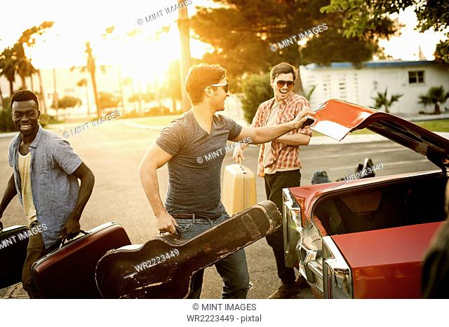 Three young men, friends packing the car with suitcases and a guitar, for a road trip