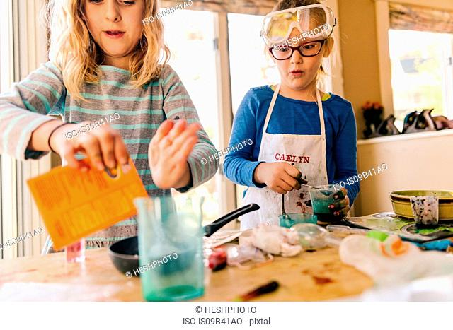 Two girls doing science experiment, pouring packet into frying pan
