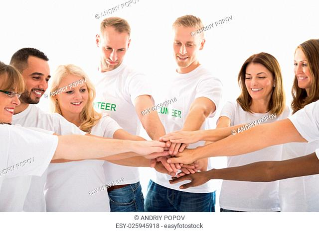 Happy multiethnic volunteers stacking hands while standing against white background