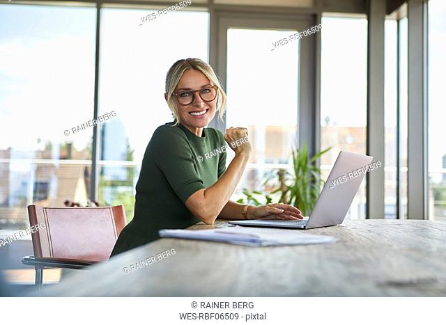 Portrait of smiling mature woman using laptop on table at home