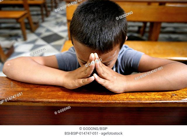 8-year-old boy praying in church