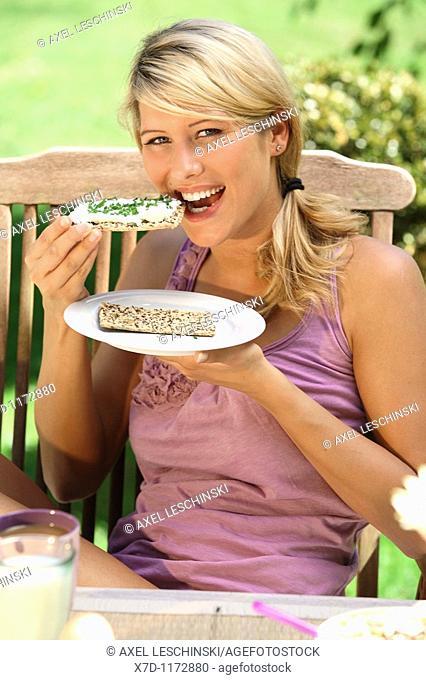 portrait of woman having breakfast in garden