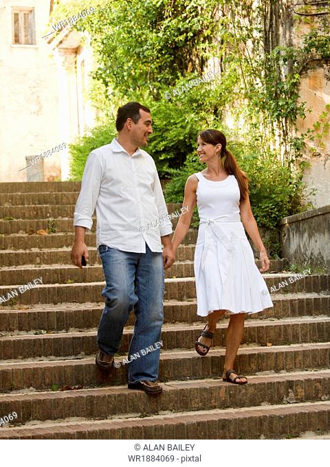 Italy, Ravello, Mature couple walking down stairs