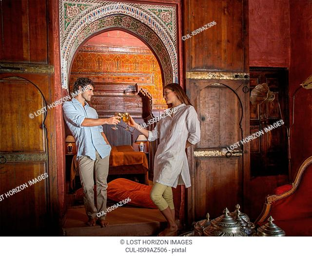 Young couple in riad making a toast in archway, Marrakesh, Morocco