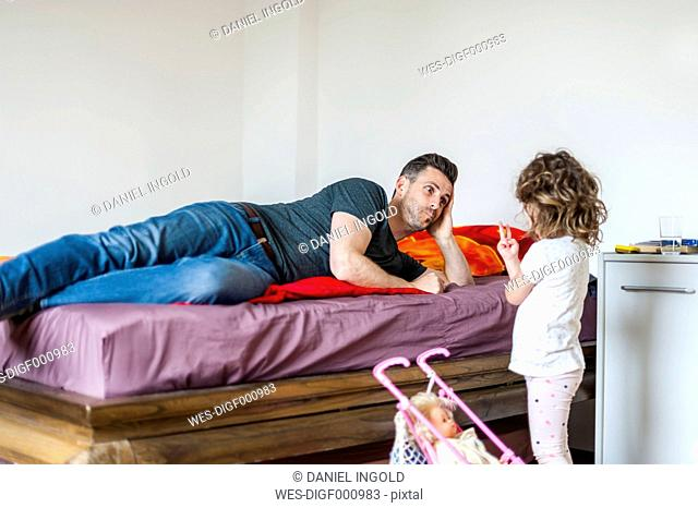 Father and daughter with doll in bedroom