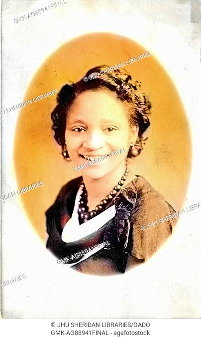Headshot of young African American woman, wearing a necklace, earrings and a dark dress with a bow, smiling, 1920. Note: Image has been digitally colorized...