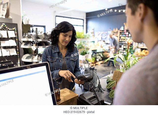Female customer paying using pin entry credit card reader at plant shop counter
