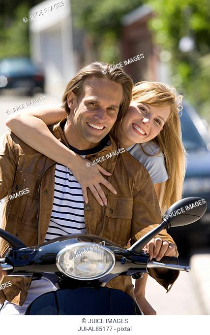 Couple smiling on motor scooter outdoors
