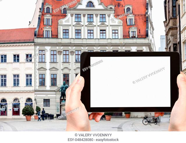 travel concept - tourist photographs of Fuggerplatz square with statue of Hans Jakob Fugger in Augsburg town in Germany on smartphone with empty cutout screen...