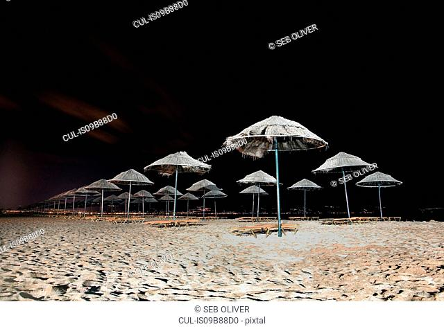 Rows of beach umbrellas and sun loungers on beach at night