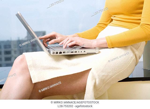 Woman using laptop near window,side view