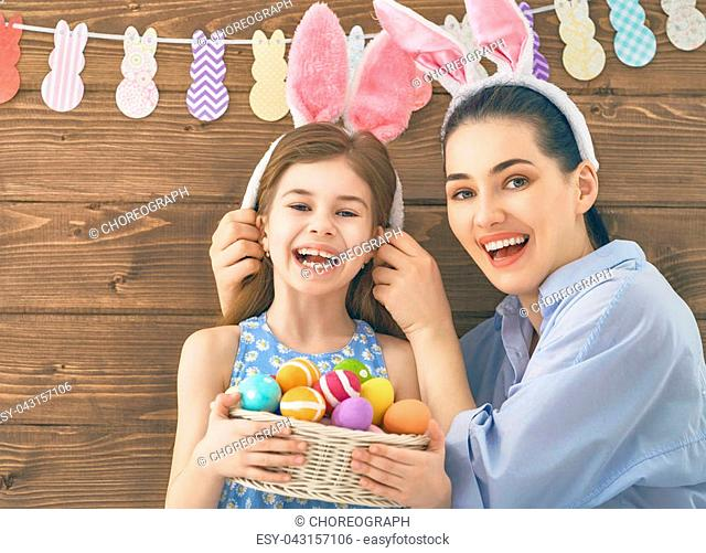 Happy holiday! Mother and her daughter with painting eggs. Family preparing for Easter. Cute little child girl is wearing bunny ears