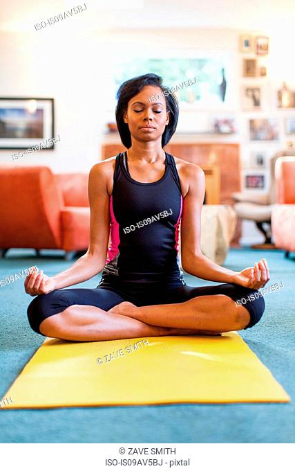Young woman sitting on yoga mat, lotus position