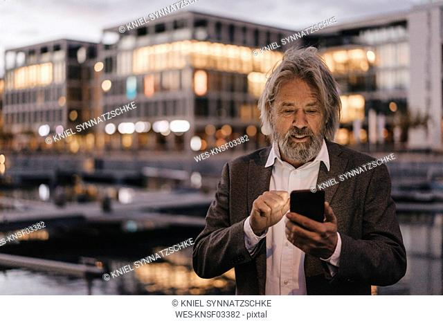 Senior man using cell phone outdoors at dusk