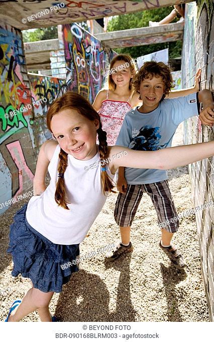 portrait of three young children at playground