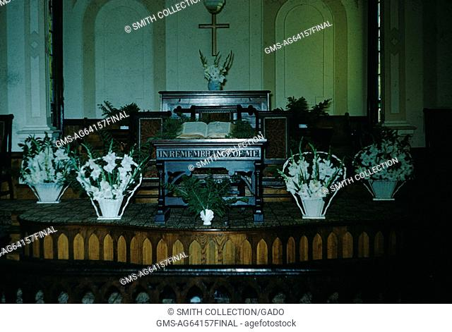 Altar of a missionary church, with bouquets of flowers, an open bible, and a sign reading In Remembrance of Me, Japan, 1952