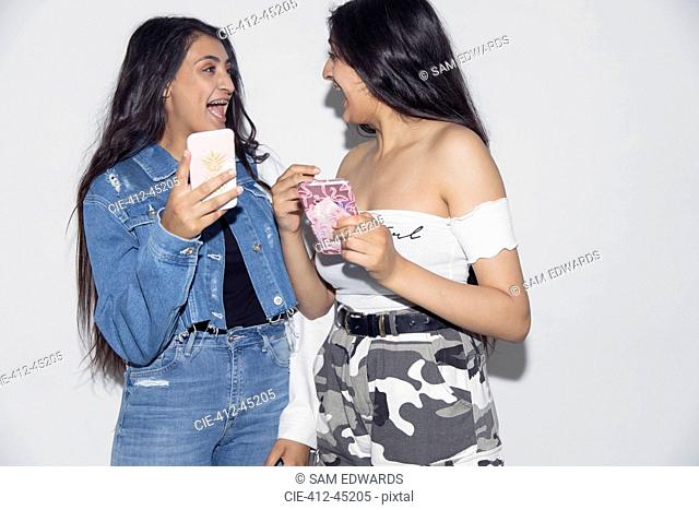 Laughing teenage twin sisters using smart phones