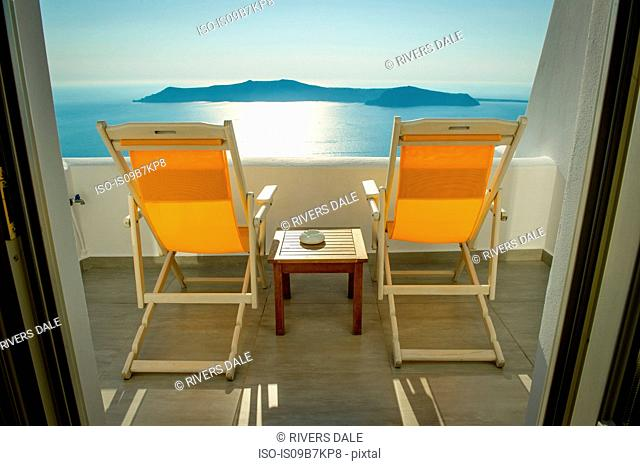 Deckchairs on balcony with view of sea, Oía, Santorini, Kikladhes, Greece