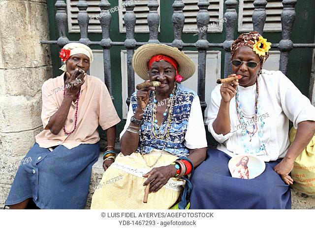 Brunettes women smoking cigars black woman representative to the Cuban typical of the time in Old Havana, Cuba