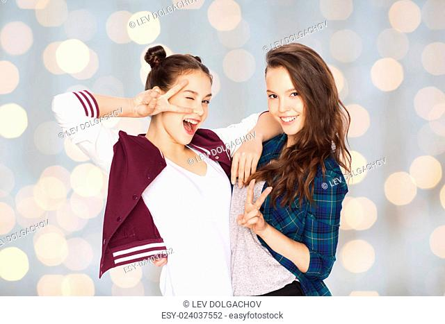 people, friends, teens and friendship concept - happy smiling pretty teenage girls showing peace hand sign over holidays lights background