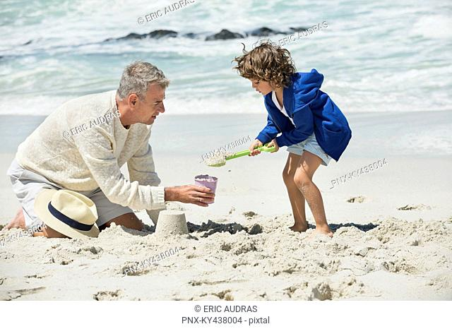 Boy playing with his grandfather on the beach