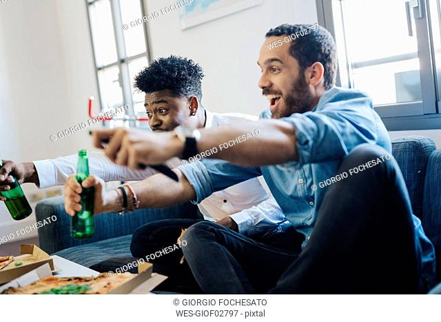 Excited friends with beer bottles sitting on the sofa cheering