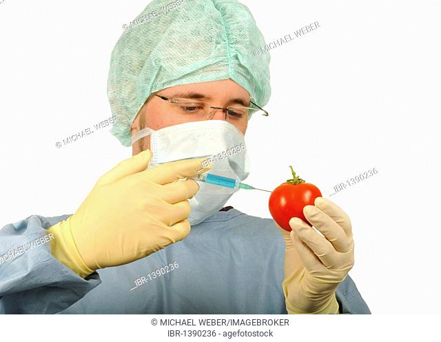 Chemist in sterile work clothes with syringe and tomato, symbolic image of genetically modified food, or food treated with pesticides