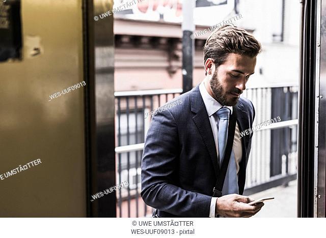 Young businessman taking metro, using smart phone