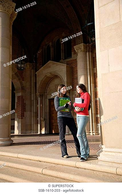 Two young women standing on a college campus