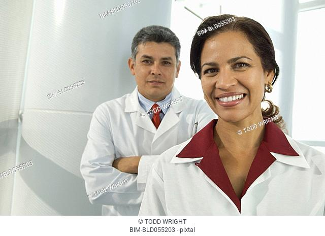 Hispanic female doctor with male doctor in background