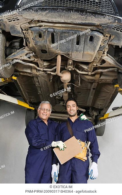 Auto mechanic with an apprentice standing under a raised car in a garage