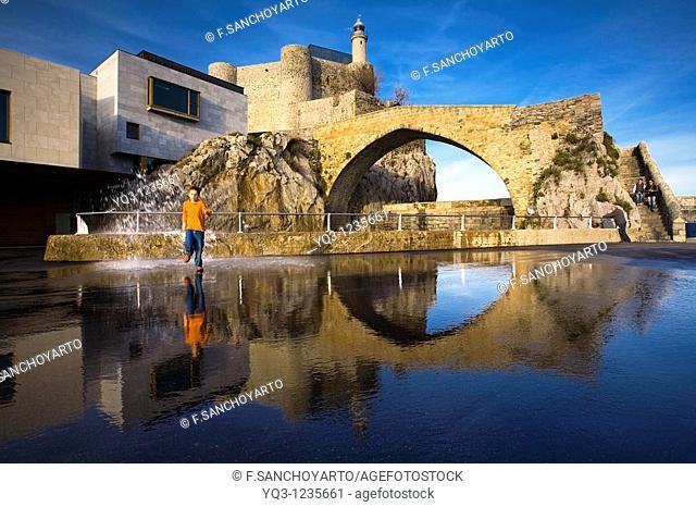 Niño chapoteando entre los reflejos del Faro y el Puente en Castro Urdiales, Cantabria
