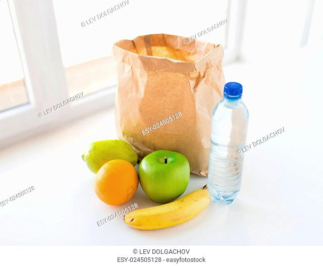cooking, diet, vegetarian food and healthy eating concept - close up of paper bag with fresh ripe juicy fruits and water bottle on kitchen table at home