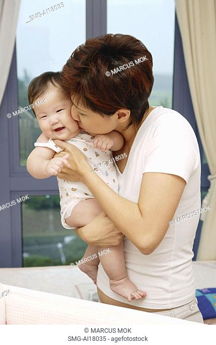 Mother kissing baby girl
