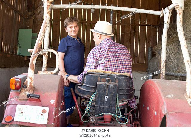 Grandfather and grandson together on a tractor