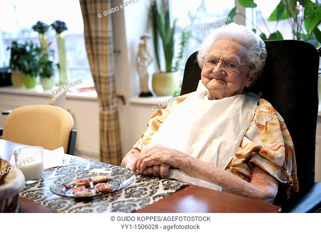 Rotterdam, Netherlands. A senior adult woman relaxing after having breakfast in the communal dining room of her nursing home, where she spends her old days