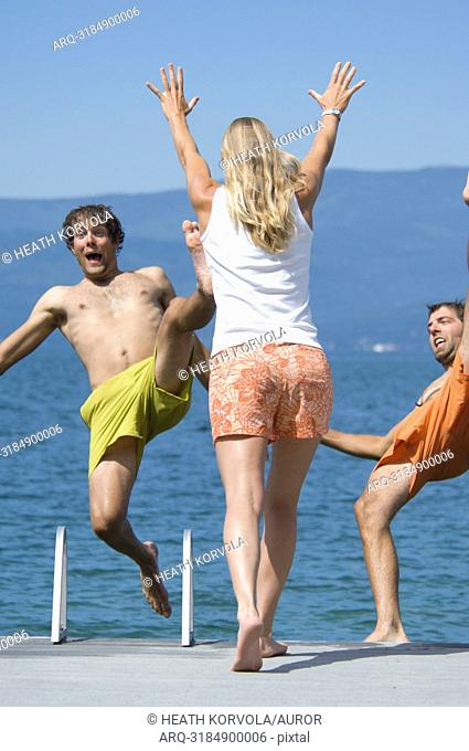 A young woman pushes her male friends into a lake