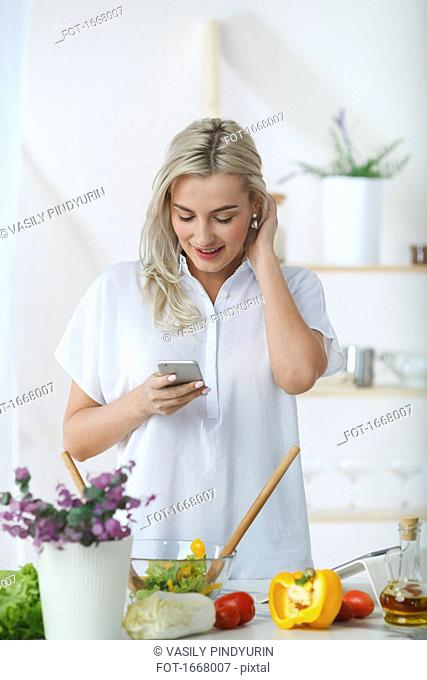 Smiling young woman using mobile phone while preparing salad at kitchen counter