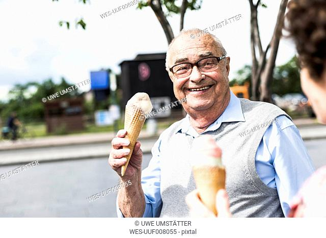 Portrait of happy senior man with ice cream cone looking at his wife