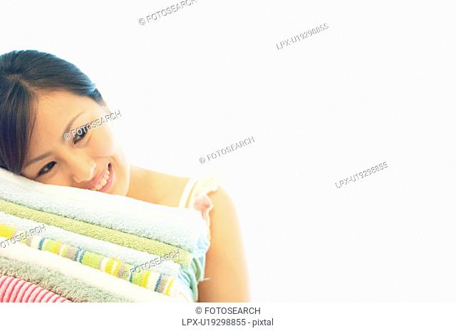 Woman resting her head against a stack of towels