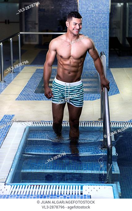 Handsome muscular man walking into pool and smiling. Vertical indoors shot