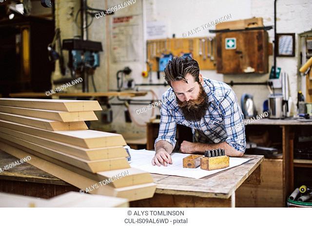 Mid adult craftsman looking down at blueprint in organ workshop