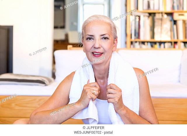 Portrait of woman with towel doing gym at home