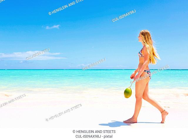 Young woman wearing bikini strolling on beach, Dominican Republic, The Caribbean