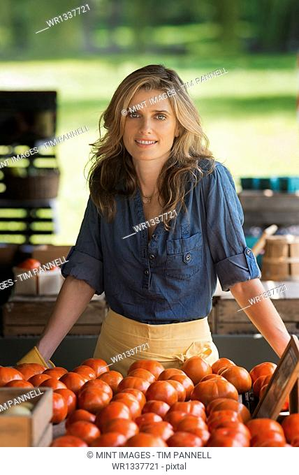 Organic farmer, a woman standing at a farm stand stall. Display of tomatoes