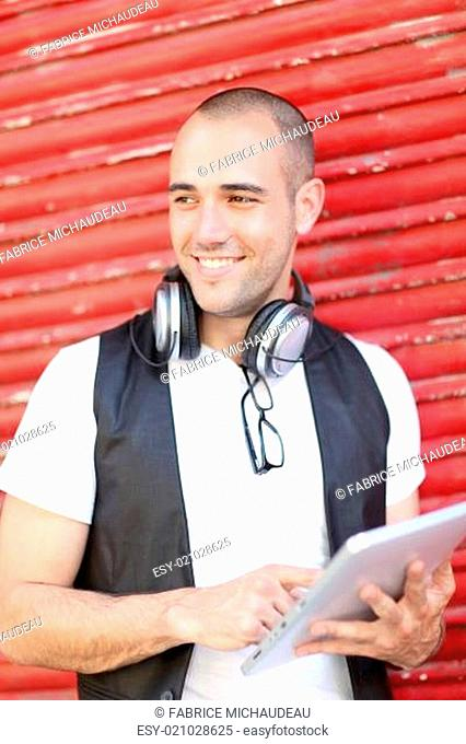 Smiling man using electronic tablet in the street