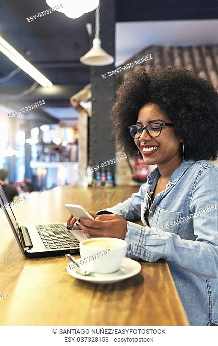 Beautiful afro american woman using mobile and laptop in the coffee shop. Communication concept