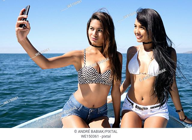 Two very attractive young hispanic women taking a cell phone selfie photo on a boat
