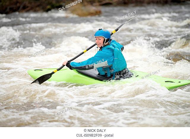 Young female kayaker paddling River Dee rapids